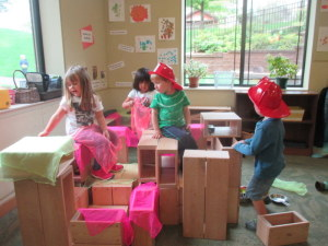 A mixed-age group plays with blocks